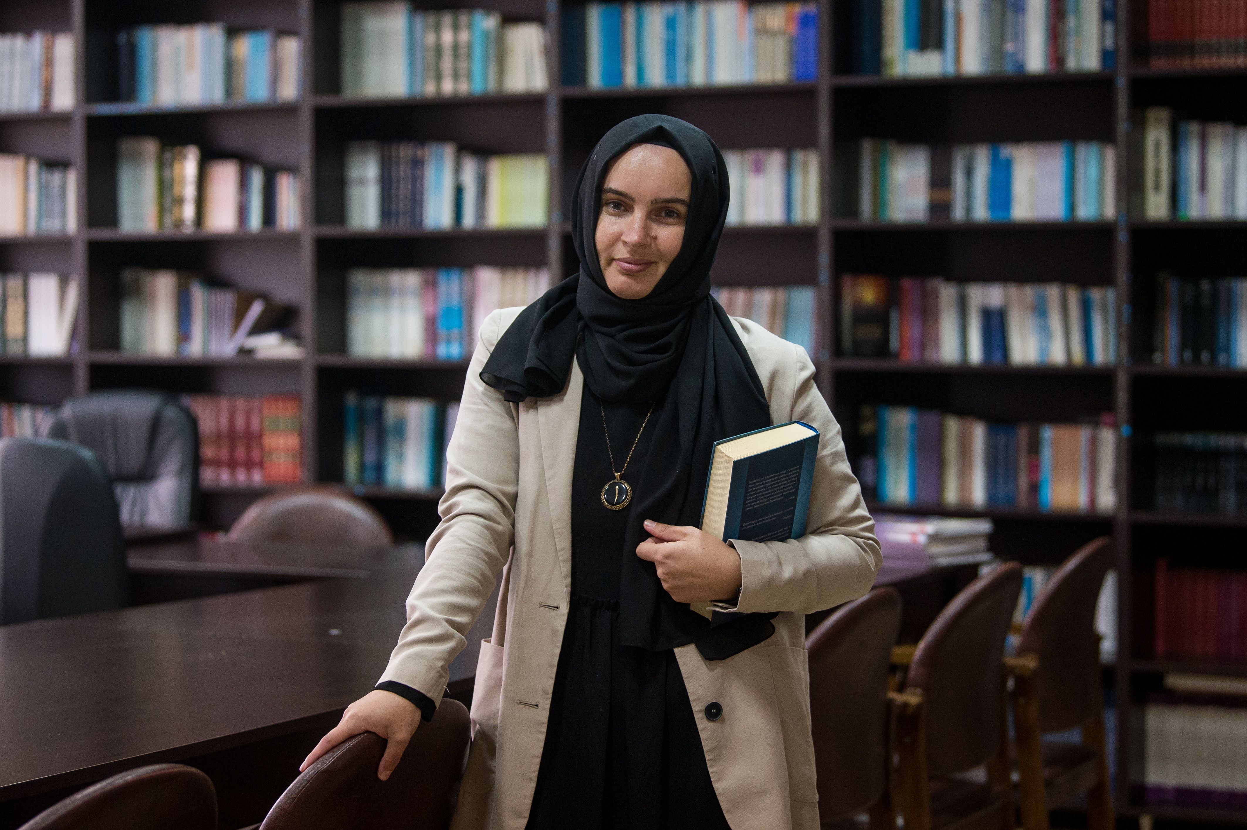 Fikrie Bozova, teacher, posses for a photo in the library of the Muslim Theological School in the town of Momchilgrad on December 6, 2020. NIKOLAY DOYCHINOV for AufRuhr
