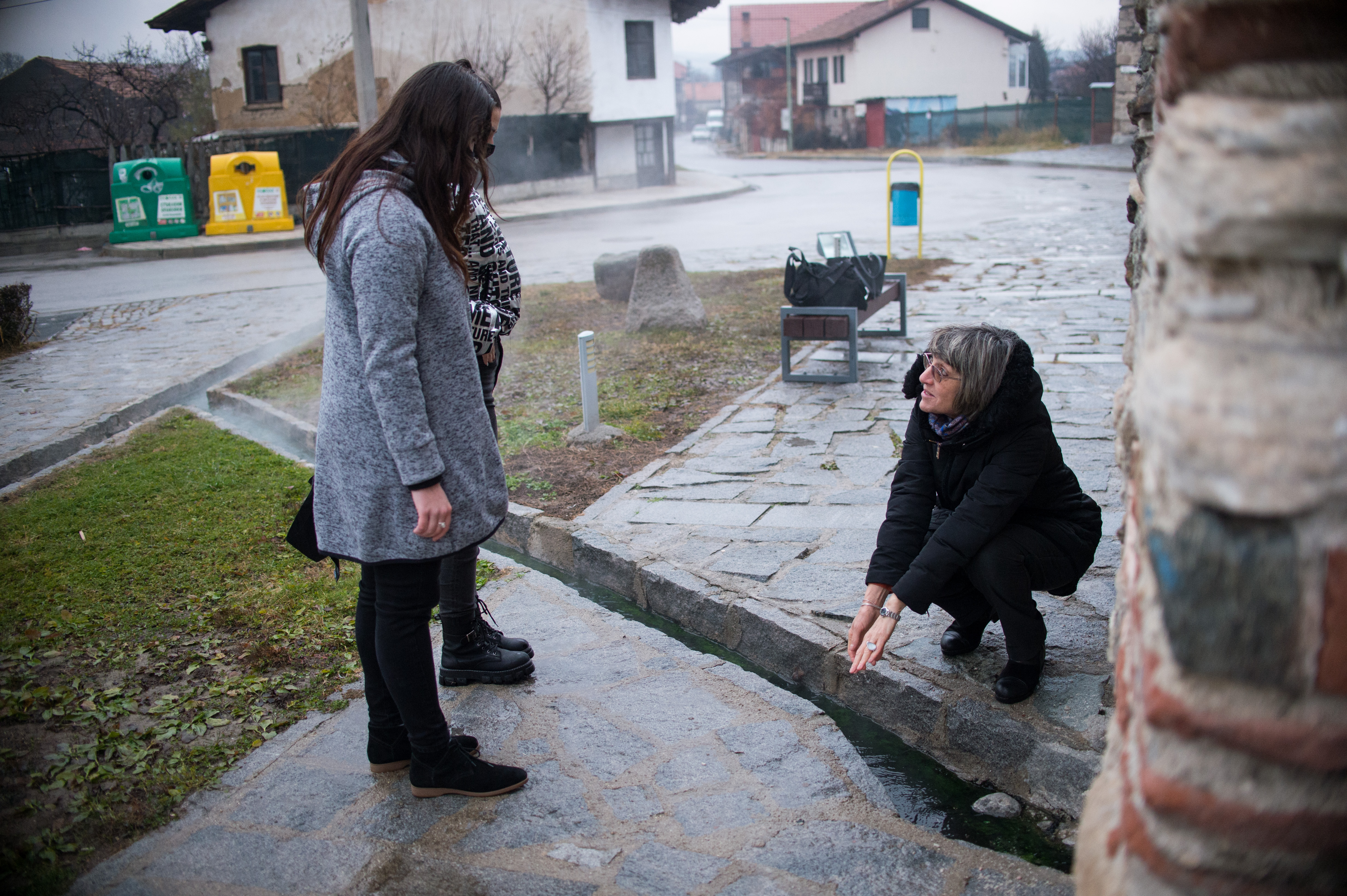 Katya Brankova, teacher, checks with two of her students a hot mineral water spring near a ancient Roman bath in the village of Banya on December 4, 2020. NIKOLAY DOYCHINOV for AufRuhr