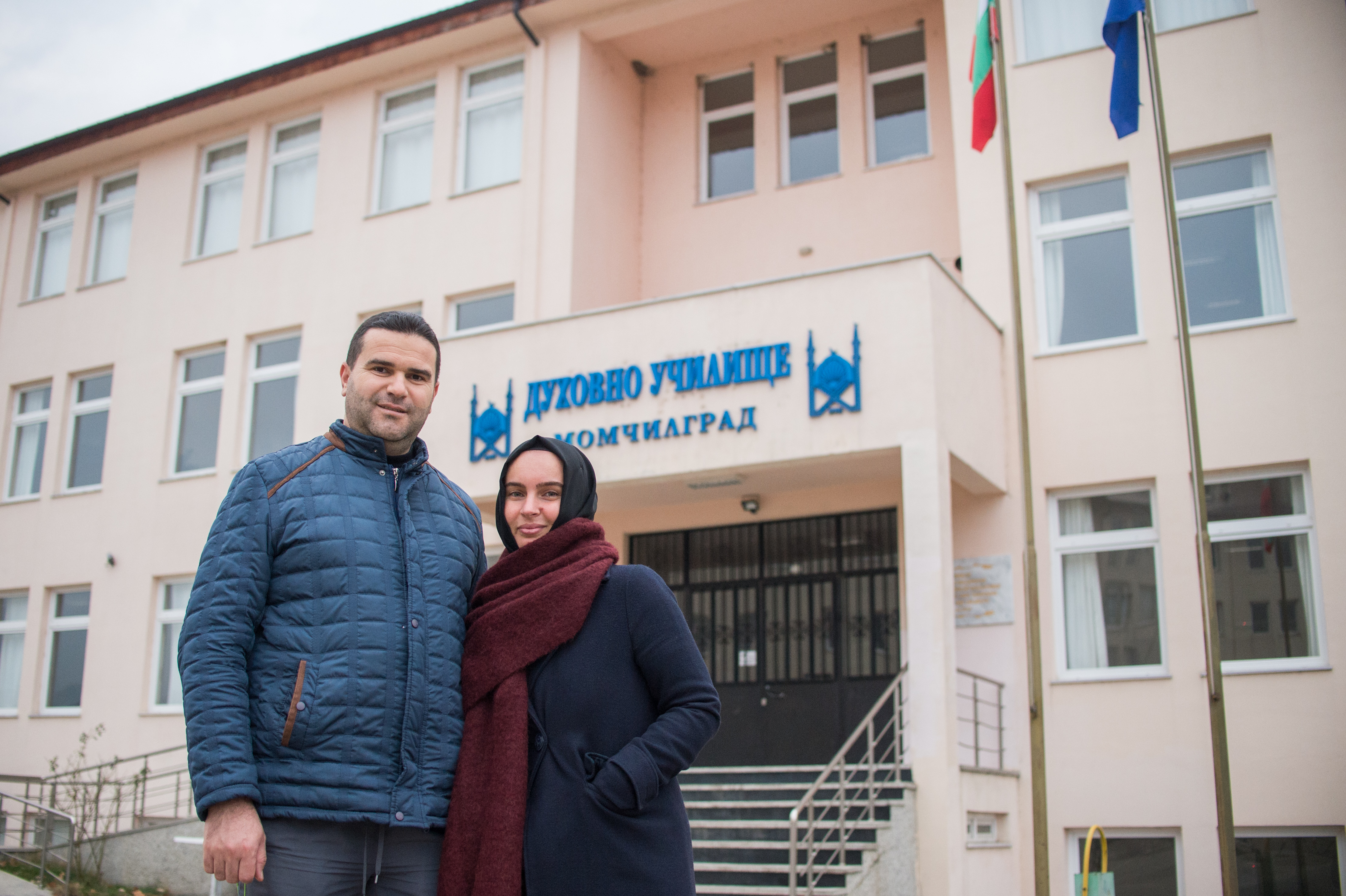 Fikrie Bozova, teacher and her husband Mehmed Bozov pose for a photo in front of the Muslim Theological School in the town of Momchilgrad on December 6, 2020. NIKOLAY DOYCHINOV for AufRuhr